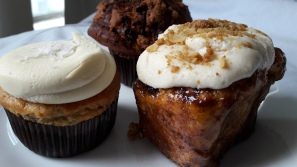 Chocolate cinnamon muffin, apple crumble bun and banana cupcake with butterscotch icing